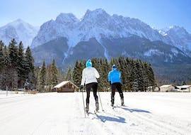 Cross-country skiers look towards the mountain and enjoy the sun's rays during their Private Cross Country Skiing Lessons - All Levels with the ski school Skischule Zugspitze-Grainau.