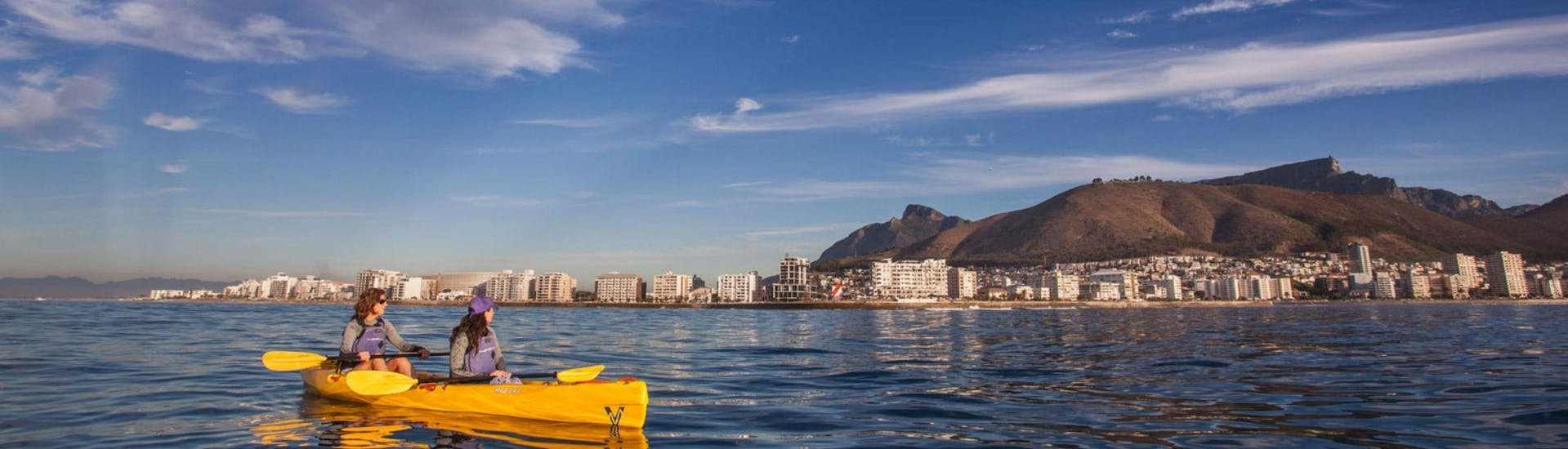 Two women are sea kayaking off the coast of Cape Town, a popular activity offered by Gravity Adventures.