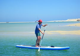 During a Guided SUP Tour in Ria Formosa Natural Park with Kite Culture Algarve, a participant is exploring the turquoise, warm waters of the lagoon.