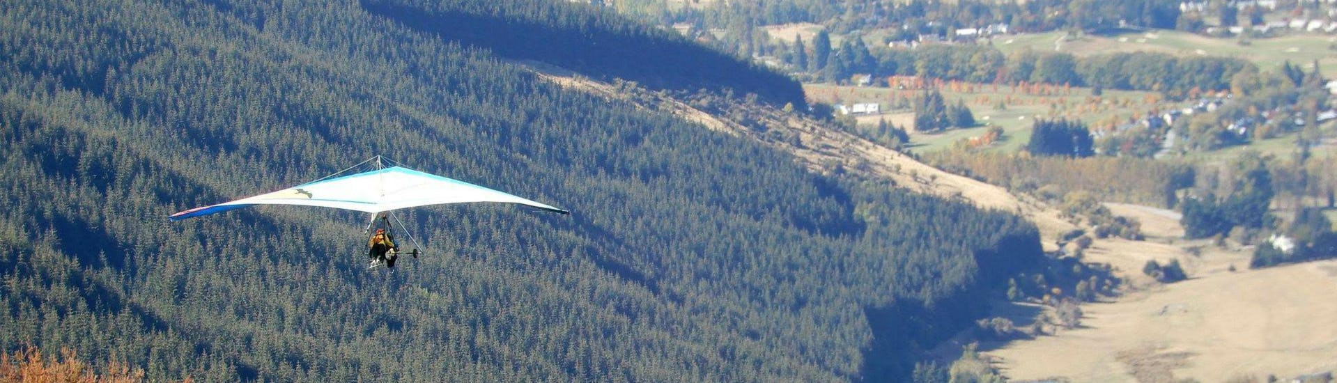 A hang glider from Skytrek Queenstown is gently floating above the woodland while Summer Hang Gliding in Queenstown.