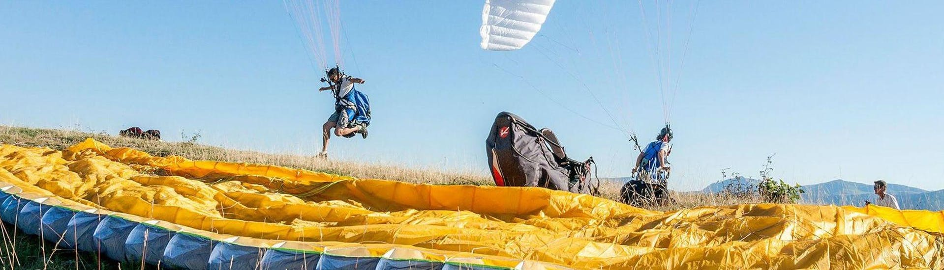 Two persons are participating to the Paragliding activity with Haut Les Mains.