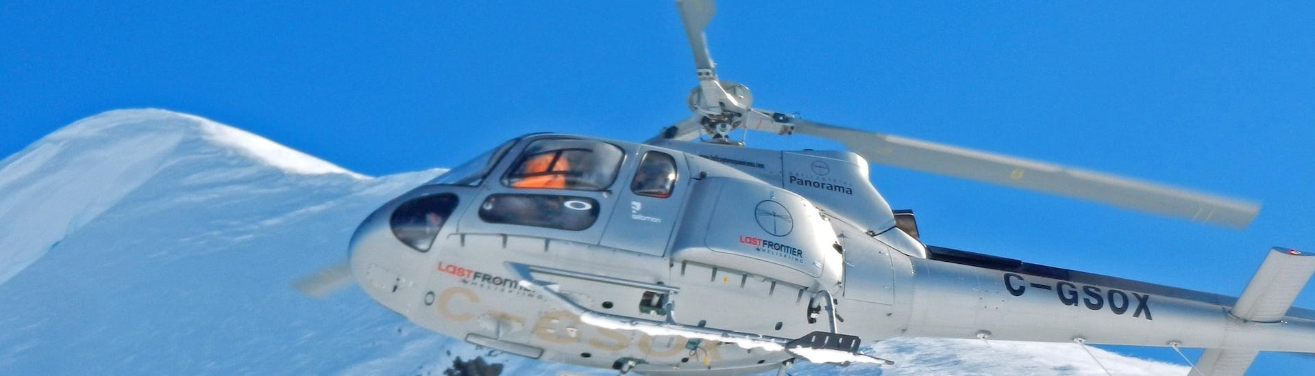 A helicopter is soaring over the snowy peaks in the ski resort of Sölden getting ready for the activity Heli Skiing Private - Mehlsack or Schneetäli organized by the ski school Alpinist in the ski resort of Sölden.