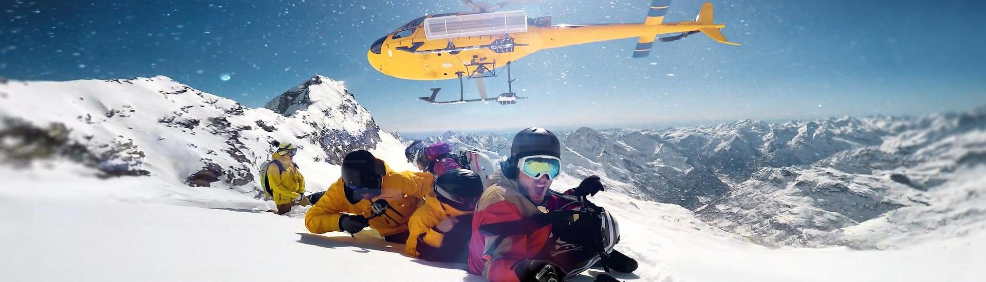 """Eine Gruppe junger Menschen liegt bei der Aktivität """"Heliskiing"""" mit dem Anbieter Wintersportschule Gerlos im Schnee am Gipfel eines Berges und macht ein Selfie mit dem Helikopter im Hintergrund."""