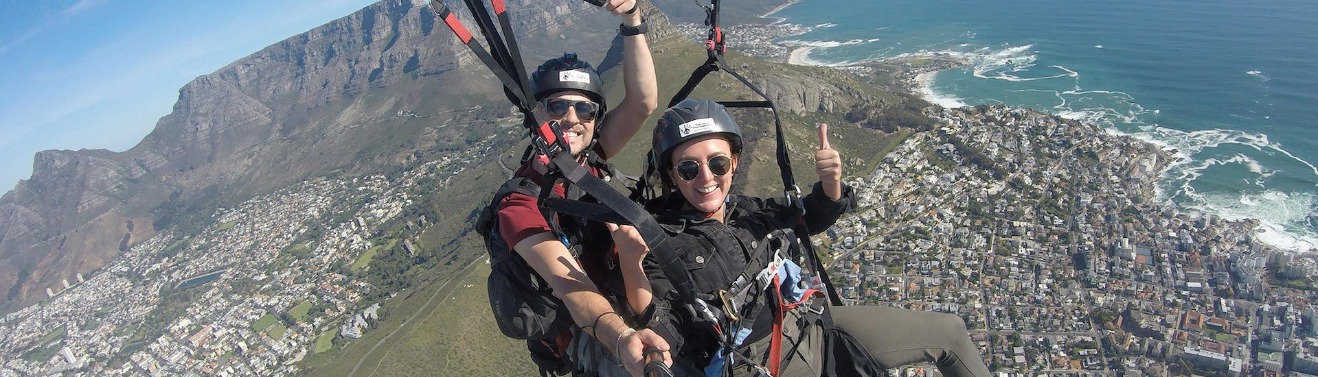 Happy woman flys with her tandem pilot over the city, enjoying the view of the sea and the mountains during paragliding in Cape Town with Hi5 Tandem Paragliding Cape Town.