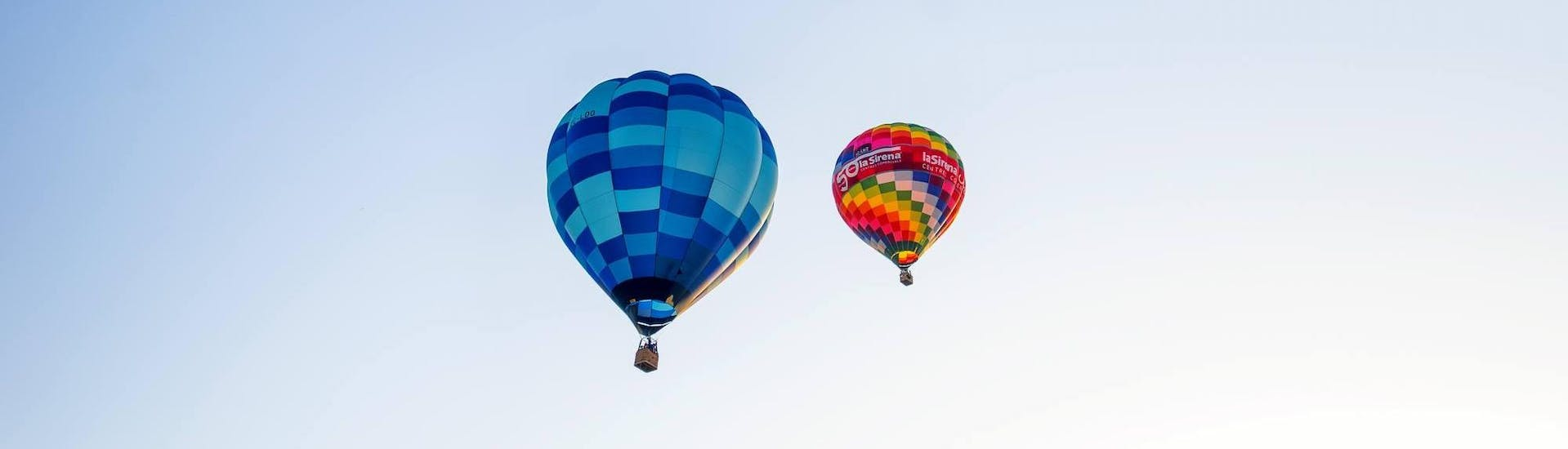 Two hot air balloons from Ibiza en Globo float several metres in the sky.