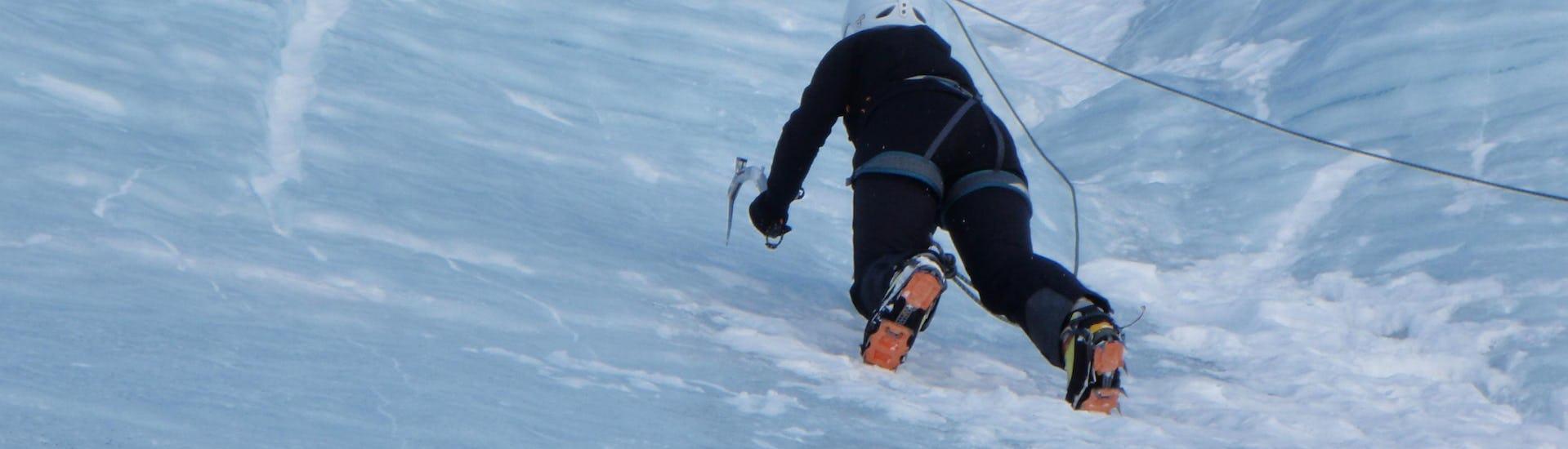 Ein Teilnehmer der von der Alpinschule Sölden organisierten Aktivität Eisklettern für Fortgeschrittene, klettert eine Eiswand im Skigebiet Sölden hoch.