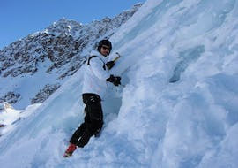 A participant of the actrivity Ice climbing for Beginners organized by the school Alpinschule Sölden is climbing an ice wall in the ski resort of Sölden.