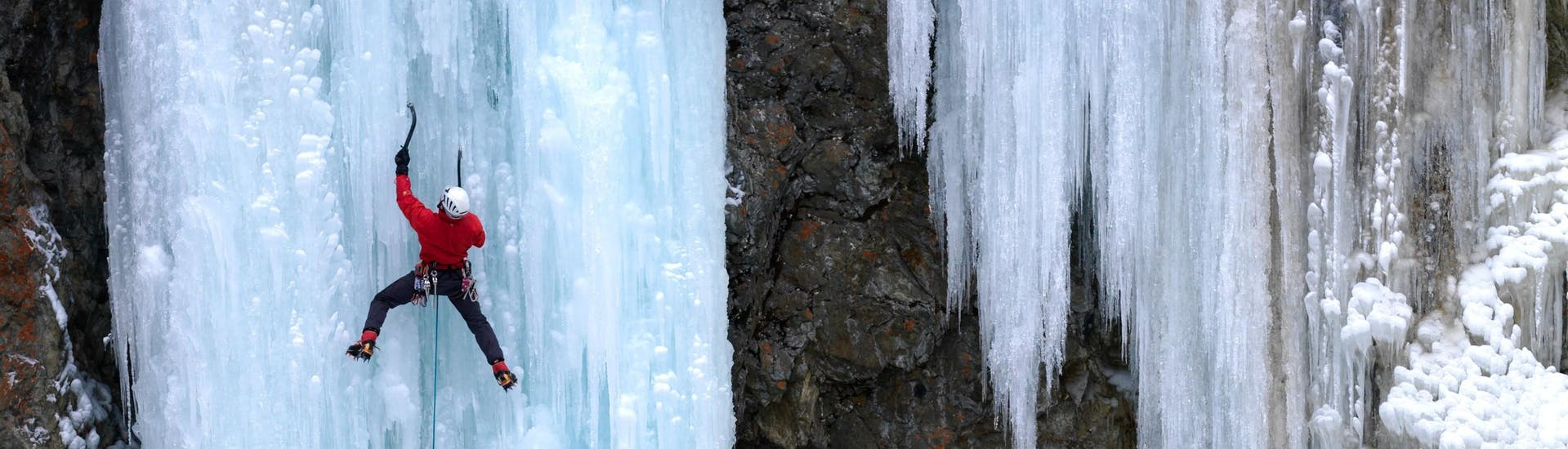A man is climbing up a a frozen waterfall during an Ice climbing for Beginners session with Alpine School Sölden.