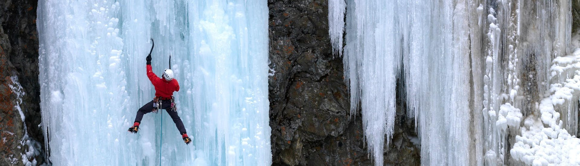A man is climbing up a a frozen waterfall during an Ice climbing - Advanced session with Alpine School Sölden.