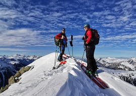 Skiers climb a peak with the Private Ski Touring Guide from Skischule Klostertal.