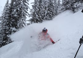 A skier is enjoying fresh powder snow during a Private Off-Piste Skiing Lessons with Skischule Klostertal.
