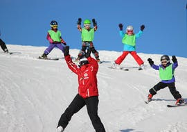 A group of children is learning to ski downhill with their ski instructor from Schweizer Skischule Zweisimmen during their Kids Ski Lessons (3-16 y.) for Beginners.