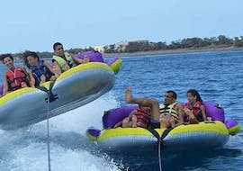 A group of friends is enjoying the thrilling ride on an inflatable boat towed by a motor boat from Crazy Sports.