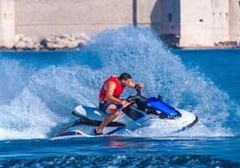 Jet ski driver from Jet Ski Rent Dubrovnik driving on the blue sea in front of Lapad, Dubrovnik.