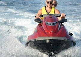 A couple has rented a powerful jet ski from Crazy Sports at Agios Georgios and is exploring the volcanic landscape of Santorini.