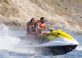 Two people ride a jet ski in Fañabé beach with Watersports Tenerife.