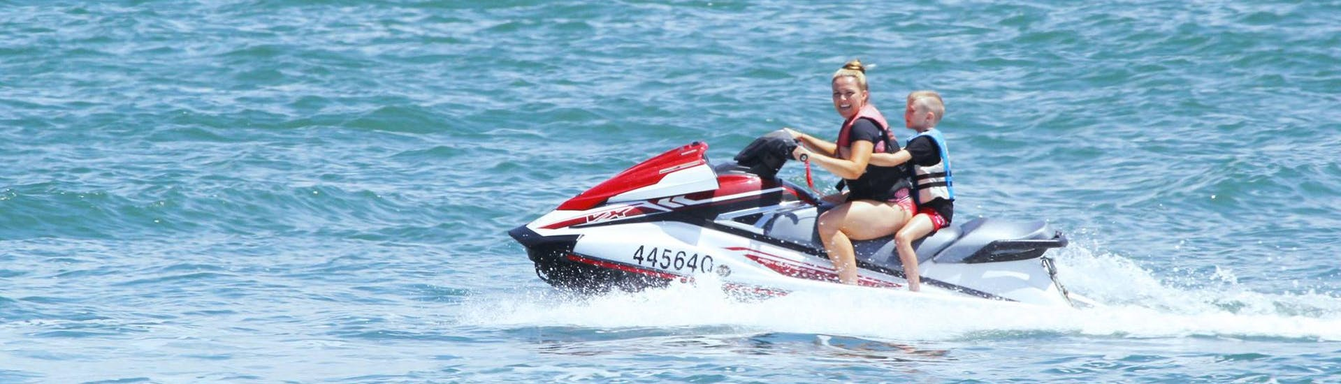 Under a supervision of an experienced instructor from Gold Coast Watersports, a mother is enjoying a jet ski ride with her son during the Jet Ski in Gold Coast - Hire.