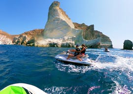 A couple is enjoying the ride across the waves during their Jet Ski Safari along the South Coast of Santorini with Kamari Beach Watersports Santorini.