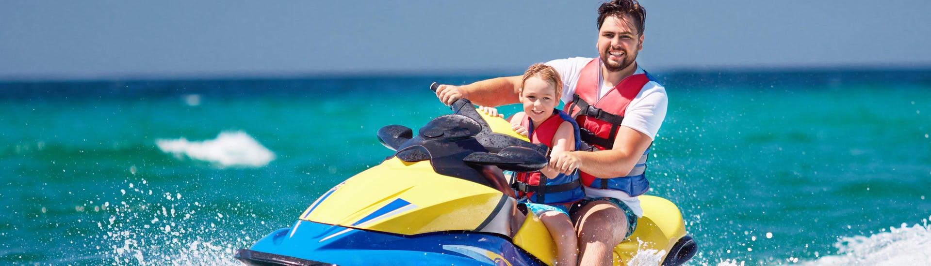 Father and daughter are having fun on a jetski