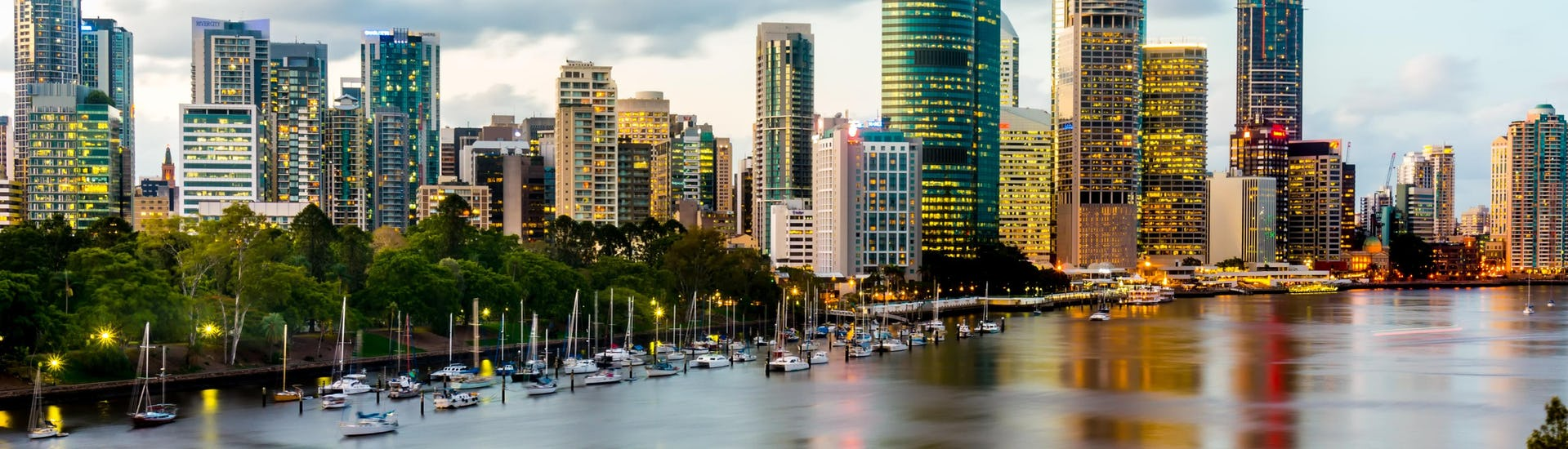 An image of Brisbane River with numerous skyscrapers lined up along its shores, something that can be seen up close when kayaking in Brisbane.