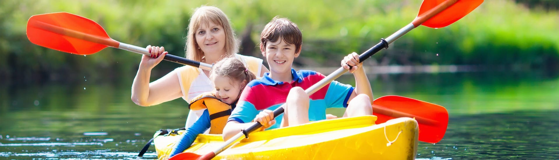 A mother and her two children are paddling across the water as they enjoy their kayak canoe in {place}.