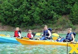 Eine Familie lächelt bei der von X Raft Val di Sole organisierten Kayak Tour für Familien auf dem Santa Guistina See in die Kamera.