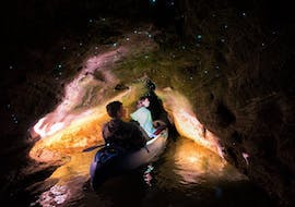 Two participants of the Kayak Rotorua - Twilight Glow Worm Tour are admiring the glow worms in a cave of the Lake Okareka during the activity organized by Paddle Board Rotorua.