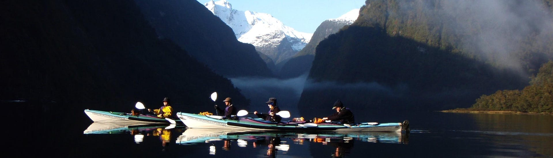 Kayakers are enjoying a peaceful moment during Kayak Tour in Doubtful Sound Fjord organized by Go Orange
