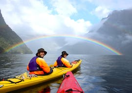 A full rainbow appears on the horizon during Kayak Tour in Milford Sound Fiord organized by Go Orange
