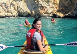 A woman paddles through the sea water and enjoys the view of impressive rock formations during the Kayak Tour to the Caves of Jávea with Snorkeling with Siesta Advisor Jávea.