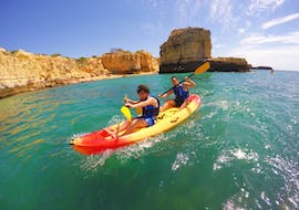 Two friends are paddling across the waves while Kayaking along the Albufeira Coast with Kayak & SUP Albufeira.