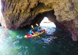 A couple is Kayaking along the Albufeira Coast with Kayak & SUP Albufeira and is exploring one of the many caves.