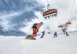 A group of snowboarders is practicing their turns with the help of their experienced instructor from Skischule Schruns during their Kids & Adult Snowboarding Lessons (from 6 y.) for All Levels.