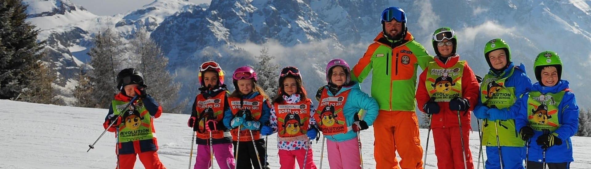 """Kinder Skikurs """"Halbtags"""" (4-13 Jahre) - Weihnachten in der Skischule Scuola di Sci AEvolution Folgarida beginnt bald, Kinder und Skilehrer posieren für ein Foto."""