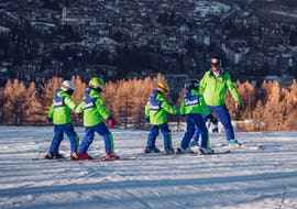 Un gruppo di bambini si diverte durante lezioni di sci per bambini (4-12 anni) - Tutti i Livelli con un simpatico istruttore della Scuola di Sci B.foxes.