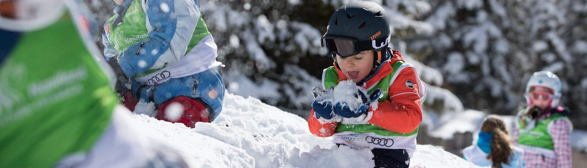 Kids are playing in the snow during Kids Ski Lessons (2-4 years) - First Timer organized by the Carezza Skischool.
