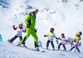 Some young skiers are following a ski instructor during the Kids Ski Lessons (3-14 years) - All Levels organized by the ski school Ski- and Bike School Ötztal Sölden in the ski area of Ötztal in Sölden.