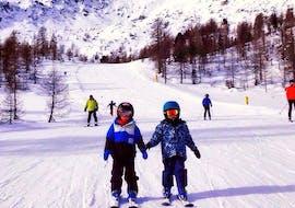 Los niños se divierten en la nieve junto con sus compañeros durante las Clases de esquí para niños (3-15 a.) para todos los niveles de Ski Life Escuela de Esquí Baqueira.