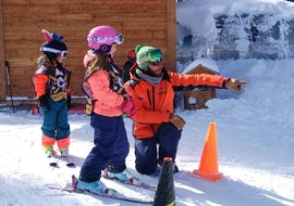 A ski instructor from the ski school Evolution 2 La Plagne Montchavin - Les Coches is giving advice to a young skier during her Kids Ski Lessons (from 3 y.) for Beginners - Christmas.