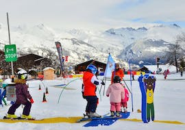 Kids are learning to ski with some games during their Kids Ski Lessons (3-4 y.) for First Timers with the ski school Evolution 2 La Plagne Montchavin - Les Coches.