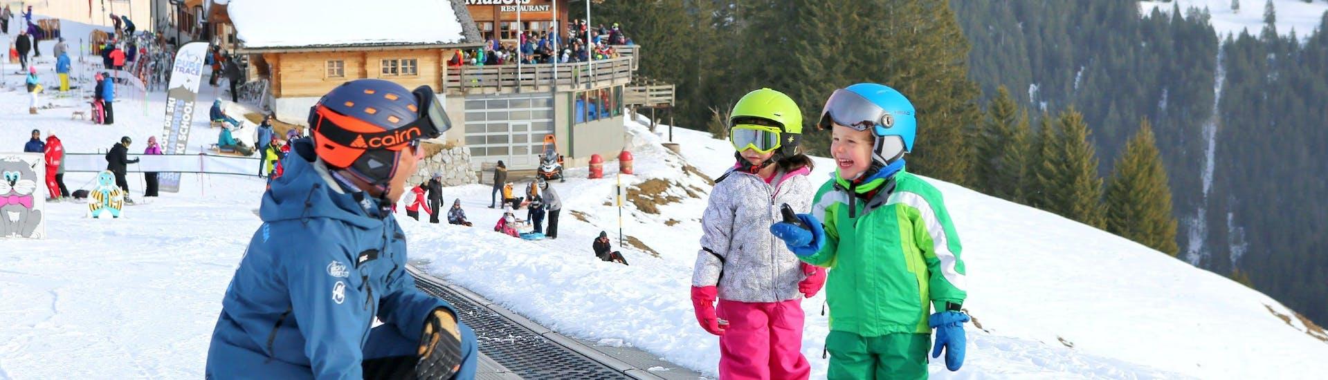 """Des enfants s'entraînent à skier dans l'aire d'entraînement pendant leur Cours de ski Enfants """"Jardin des Neiges"""" (3-4 ans) avec l'école de ski Diablerets Pure Trace."""