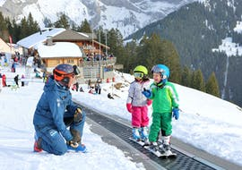 "Children practice skiing on the practice area during their Kids Ski Lessons ""SnowGarden"" (3-4 y.) with the ski school Diablerets Pure Trace."