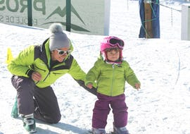 A little child takes the first steps on skis during the Kids Ski Lessons (3-4 years) - Beginner in the safe environment of the ski school Prosneige Val d'Isère.