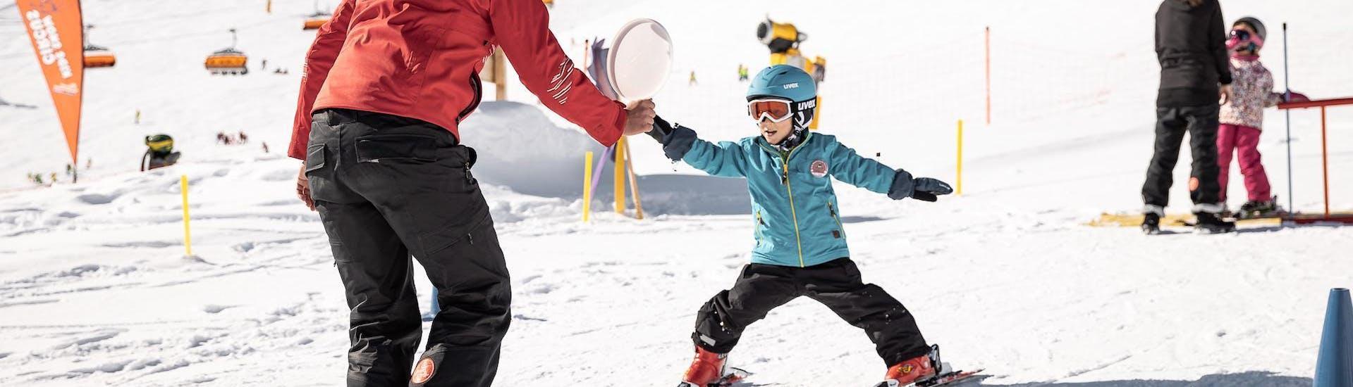 Ein kleines Kind meistert beim Kinder Skikurs (3-4 Jahre) für Anfänger seine ersten Schritte auf den Skiern mit einer erfahrenen Skilehrerin der Ski- & Snowboardschule Vacancia.