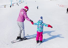 A ski instructor holds a child in her hand during one of the kids ski lessons (3-5 years) for first timer at the Ski School Scuola di Sci Abetone.