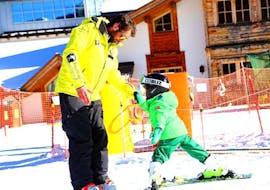 A ski instructor of Maestri di sci Moena ski school teaching a kid how to ski during the Kids Ski Lessons (3-5 y.) for beginners.