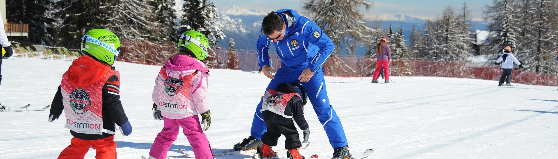 Kids Ski Lessons (3-5 years) - First Timer of Folgarida Dimaro Ski School are taking place, the children are training on the slopes of Val di Sole with the ski instructor.