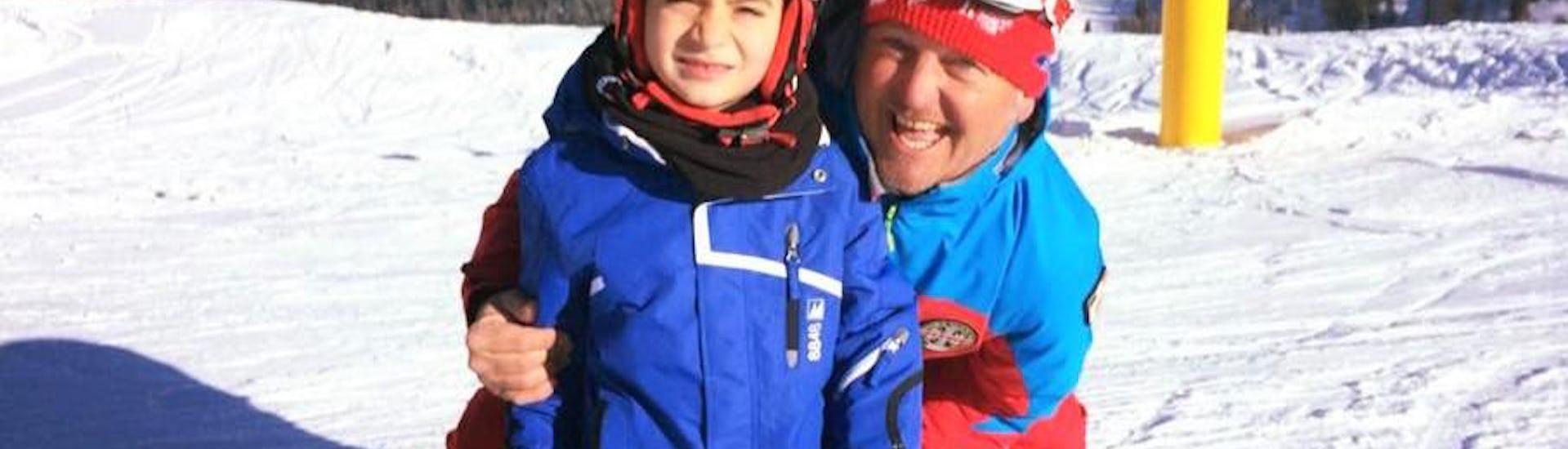 Ein Kind lächelt während dem von der Skischule Scuola di Sci Val Rendena organisierten Kinder Skikurs (3-5 J.) - Anfänger auf den Pisten von Pinzolo gemeinsam mit seinem Skilehrer in die Kamera.