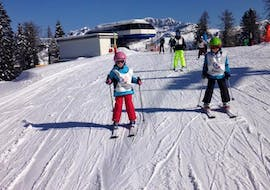 A young skier is learning how to master a slope during the Kids Ski Lessons (3-5 y.) - First Timer - Holidays organized by the ski school Scuola di Sci Val Rendena in the ski resort of Pinzolo.