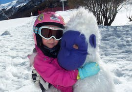 A kid is hugging the Yeti mascot of the ski school Evolution 2 Val d'Isère during their Kids Ski Lessons (3-5 years) - Morning - Beginner.
